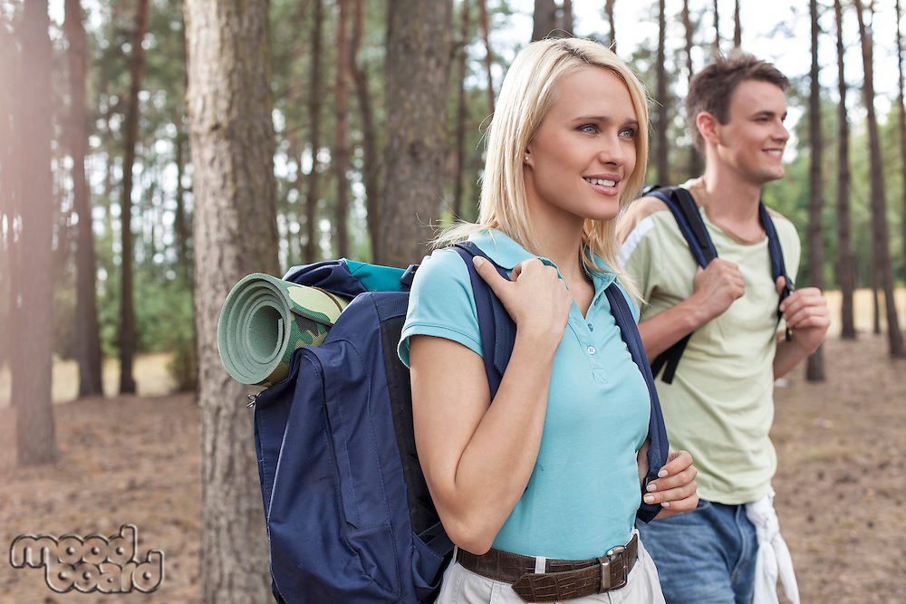 Happy young female backpacker with man hiking in woods