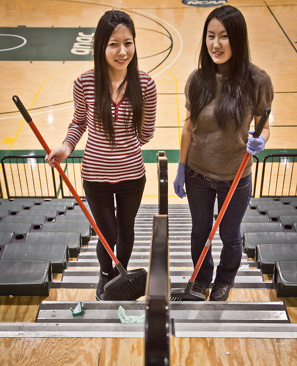 UAA foreign students from Mongolia, Toma Damba and Sanna Ganchuluun, help clean up after a UAA Basketball game.