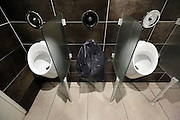 one broken urinal in a row of three