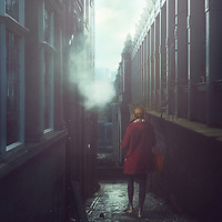 young woman wearing red coat walking alone in street