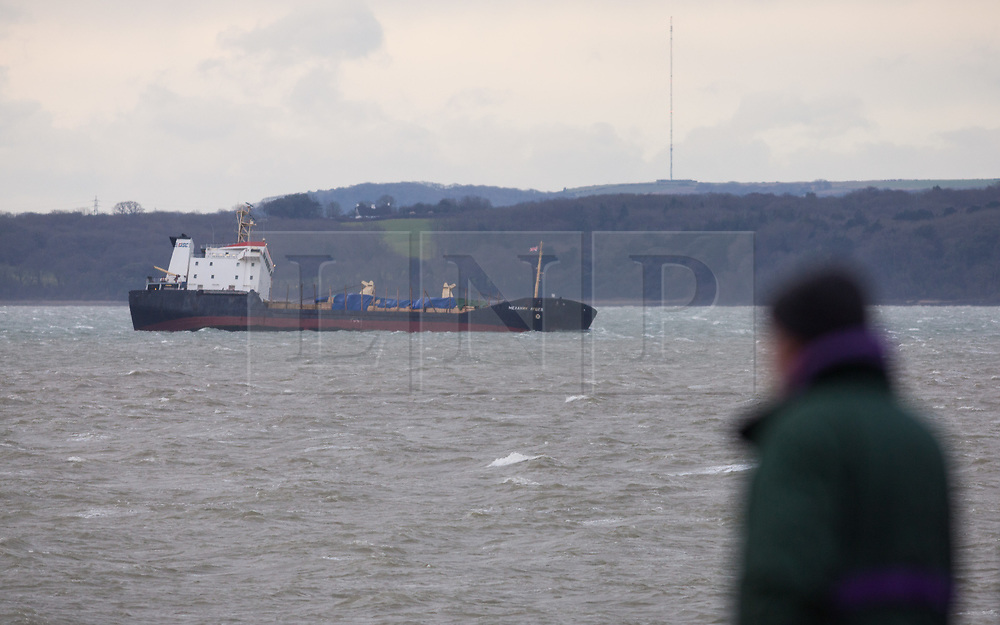 © Licensed to London News Pictures. 27/12/2017. Lee-on-Solent, UK.  A man looks on at the stricken Russian cargo vessel, Mekhanic Yartsev, as she braces the strong winds in The Solent this morning. The Maritime and Coastguard Agency are formulating a plan to move her to Southampton. 13 crew members were rescued yesterday when the vessel developed a list, so made her way into the sheltered waters of The Solent before the weather conditions deteriorated. Photo credit: Rob Arnold/LNP