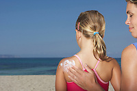 Mother applying sunscreen to daughter's (5-6) back back view