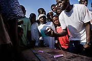 Children and young men gather around a man who plays card tricks during annual Oguaa Fetu Afahye Festival in Cape Coast, Ghana on Saturday September 6, 2008...