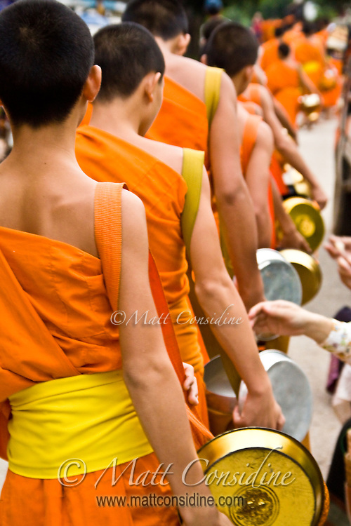 Monks walk in single file through the town every morning, each accepting a small amount of food from devotees.<br /> (Photo by Matt Considine - Images of Asia Collection)