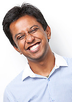 Portrait of happy young Indian man against white background