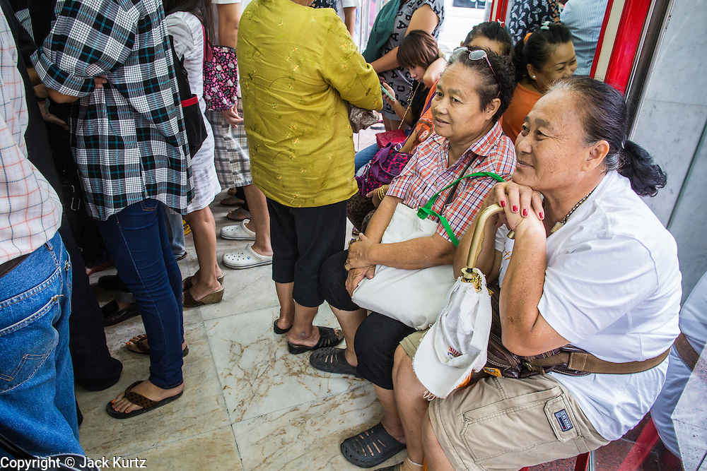 17 APRIL 2013 - BANGKOK, THAILAND:   Women wait to buy gold in a Bangkok gold shop. Thais flocked to gold shops in Bangkoks's Chinatown this morning to buy gold. Wednesday was the first day most gold shops were open after a five day holiday weekend. Shops were closed Friday through Tuesday, when global gold prices dropped by more than 13% based on jitters that Cyprus might liquidate its gold stocks. The Thailand Futures Exchange (TFEX) suspended trading of all gold and silver futures for a short time Tuesday morning because of instability in the market. Gold is now about 22 percent below the record peak of $1,920.30 an ounce set in September 2011. Thais buy gold as both jewelry and an investment, a hedge against inflation and financial failures. Bangkok's Chinatown district is the center of Thailand's gold trade.  PHOTO BY JACK KURTZ