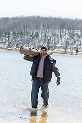 rugged handsome man walking in a lake while carrying a log during the Wintertime