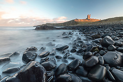 The winter sun lights up Dunstanburgh Castle on the Northumberland coast