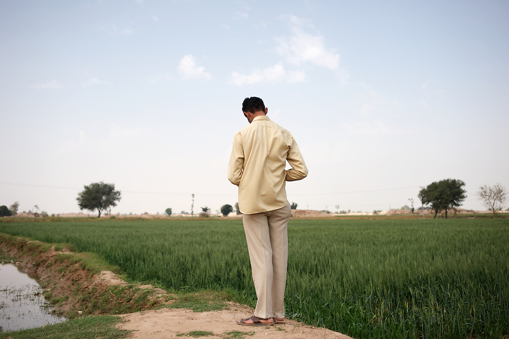 A man stands on the side corner of agricultural fiels in village 109. Being a very male dominated society, Pakistans rural side is still mostly ruled and owned by feudals and women are seen as second hand citizens. Khanpur, Pakistan, 2010
