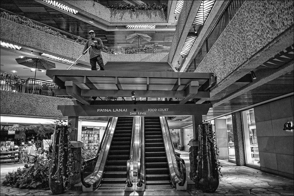 Jim, (no last name) night maintenance at Royal Hawaiian Shopping Center sweeps roof over escalators. 1:51am