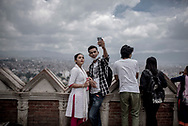 """Visitors take a selfie in Swayambhunath, an ancient religious temple in Kathmandu Valley.  The flood of tourists coming in along with the power of the new technologies are inspiring young Nepalese women and men to adopt a more """"westernized"""" way of life, and are finding ways to combining it with the old Nepalese culture. In Nepal arranged marriages between the same cast are the most common system, but love marriages are becoming more popular every day, especially in urban areas."""