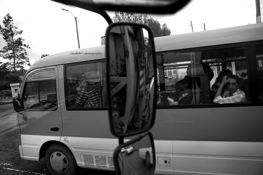 """Public bus transport in Shushi. This image is part of the photoproject """"The Twentieth Spring"""", a portrait of caucasian town Shushi 20 years after its so called """"Liberation"""" by armenian fighters. In its more than two centuries old history Shushi was ruled by different powers like armeniens, persians, russian or aseris. In 1991 a fierce battle for Karabakhs independence from Azerbaijan began. During the breakdown of Sowjet Union armenians didn´t want to stay within the Republic of Azerbaijan anymore. 1992 armenians manage to takeover """"ancient armenian Shushi"""" and pushed out remained aseris forces which had operate a rocket base there. Since then Shushi became an """"armenian town"""" again. Today, 20 yeras after statement of Karabakhs independence Shushi tries to find it´s opportunities for it´s future. The less populated town is still affected by devastation and ruins by it´s violent history. Life is mostly a daily struggle for the inhabitants to get expenses covered, caused by a lack of jobs and almost no perspective for a sustainable economic development. Shushi depends on donations by diaspora armenians. On the other hand those donations have made it possible to rebuild a cultural centre, recover new asphalt roads and other infrastructure. 20 years after Shushis fall into armenian hands Babies get born and people won´t never be under aseris rule again. The bloody early 1990´s civil war has moved into the trenches of the frontline 20 kilometer away from Shushi where it stuck since 1994. The karabakh conflict is still not solved and could turn to an open war every day. Nonetheless life goes on on the south caucasian rocky tip above mountainious region of Karabakh where Shushi enthrones ever since centuries."""