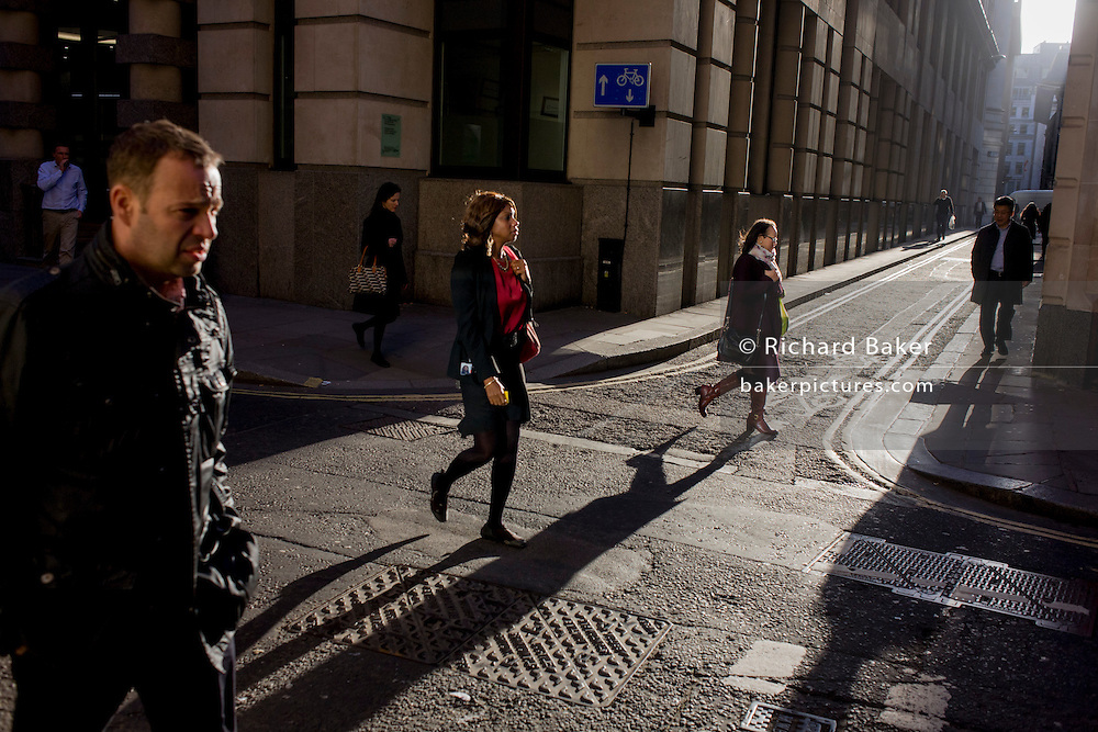 Businessmen and women walk through winter sunlight on the corner of Lombard Street and Abchurch Lane, EC4, in the City of London.