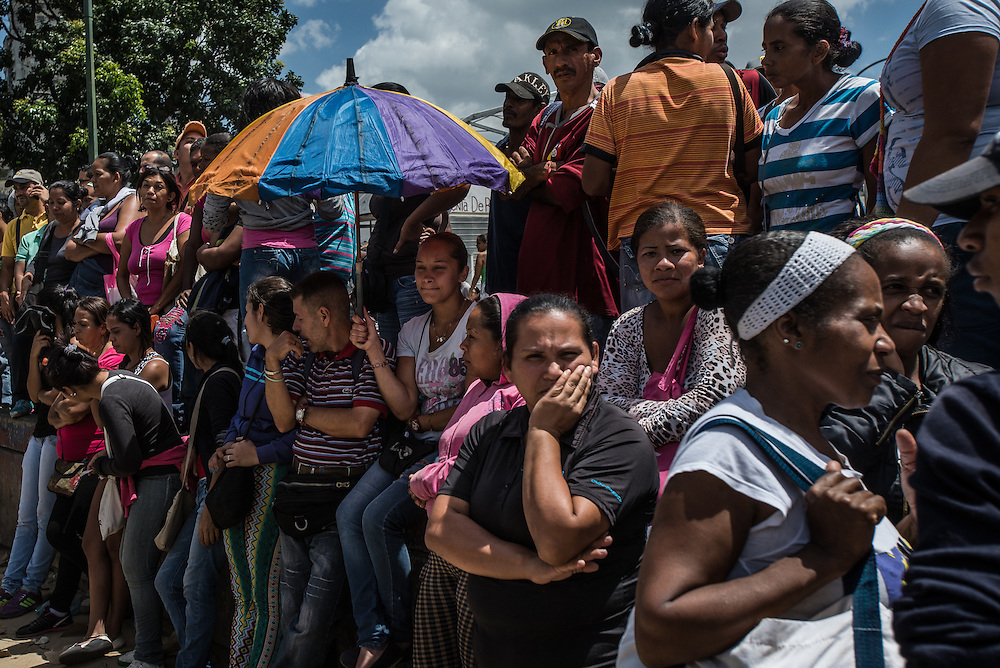 """CARACAS, VENEZUELA - JUNE 11, 2016:  Hundreds of people wait in line to buy food outside of a grocery store in Catia, a slum in western Caracas. The shoppers had arrived as early as 3 am, and waited in line for over eight hours before they were told to go home because there was no more food available for them to buy.  Dozens of people in the line started to protest, exasperated by being told to go home empty handed, after waiting for so long.  When the crowd became unruly, armed """"collectivos"""" of government loyalists arrived and threatened them, beating one man. The protesting shoppers refused to stop, shouting """"we are hungry!"""" until anti-riot police arrived and calmed everyone down.  PHOTO: Meridith Kohut for The New York Times"""