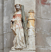 Polychrome stone statue of St Barbara, early 16th century, holding the martyrs' palm and with the tower, her attribute, in the Collegiale Notre-Dame de Poissy, a catholic parish church founded c. 1016 by Robert the Pious and rebuilt 1130-60 in late Romanesque and early Gothic styles, in Poissy, Yvelines, France. Saint Louis was baptised here in 1214. The Collegiate Church of Our Lady of Poissy was listed as a Historic Monument in 1840 (this statue is also listed as a protected object) and has been restored by Eugene Viollet-le-Duc. Picture by Manuel Cohen