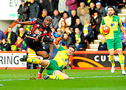 AFC Bournemouth forward Benik Afobe gets a shot away under pressure from  Norwich City defender Ryan Bennett during the Barclays Premier League match between Bournemouth and Norwich City at the Goldsands Stadium, Bournemouth, England on 16 January 2016. Photo by Graham Hunt.