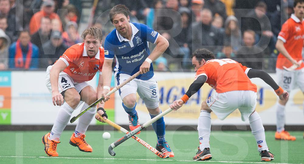 BLOEMENDAAL - HOCKEY - Joost Van de Vijfeijken (m) van Kampong passeert Mats de Groot (l) en Diede van Puffelen van Bl'daal.   Eerste  wedstrijd play offs in de hoofdklasse hockey competitie tussen de mannen van Bloemendaal en Kampong (2-3) . COPYRIGHT KOEN SUYK