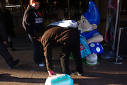 A gnome cartoon character appears to be sniffing the behind of a passer-by bending to pick up possessions in a London Street.
