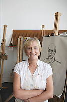 Artist standing by artwork in studio portrait
