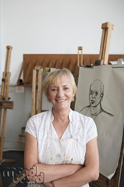 Artist standing by artwork in studio portrait