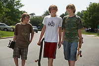Three teenage brothers (13-17) walking on street carrying skateboards