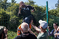 An environmental activist climbs over a HS2 security fence during the restaging of a historical 1602 visit by Queen Elizabeth I to Dews Farm on 31st July 2020 in Harefield, United Kingdom. The activists tried to retrace the steps of Queen Elizabeth I from St Mary's church to Dews Farm in order to pay their respects to Anne and Ron Ryall, 73 and 72, on the day of their eviction from Dews Farm by HS2 after having spent nine years and their life savings renovating their £1m dream home, but found their path blocked by HS2 fences and security guards.