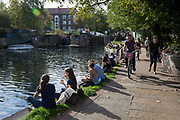 Londoners enjoy an autumnal Indian Summer on the Regent's Canal towpath in Hackney, on 16th October 2018, in London, England.