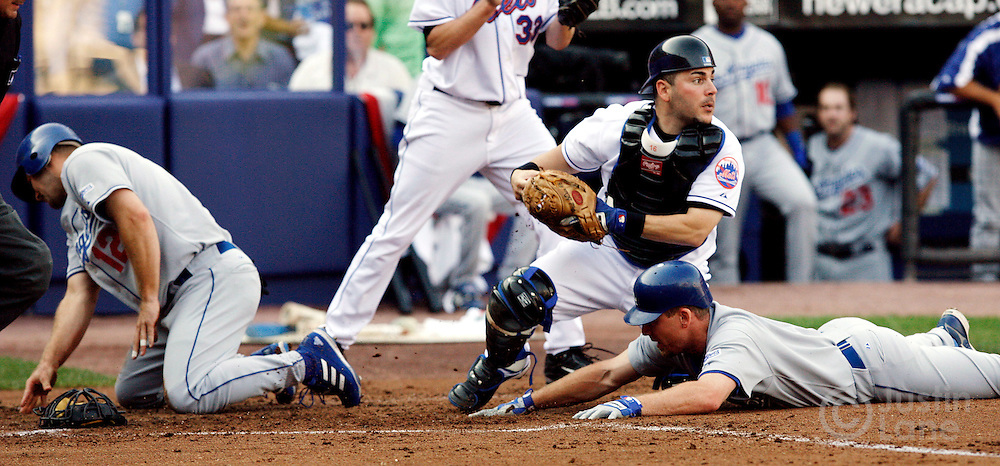 epa00833739 New York Mets catcher Paul Lo Duca (2nd from R) tags out the Los Angeles Dodgers' J.D. Drew (R) after tagging out Jeff Kent (L) at home plate during the second inning of game one of the National League Division Series between the Los Angeles Dodgers and the New York Mets at Shea Stadium in Flushing Meadows, New York on Wednesday 04 October 2006. In the background is New York Mets pitcher John Maine.  EPA/JUSTIN LANE