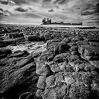 Dunstanburgh Castle in northern England beach scene with rocky coastline