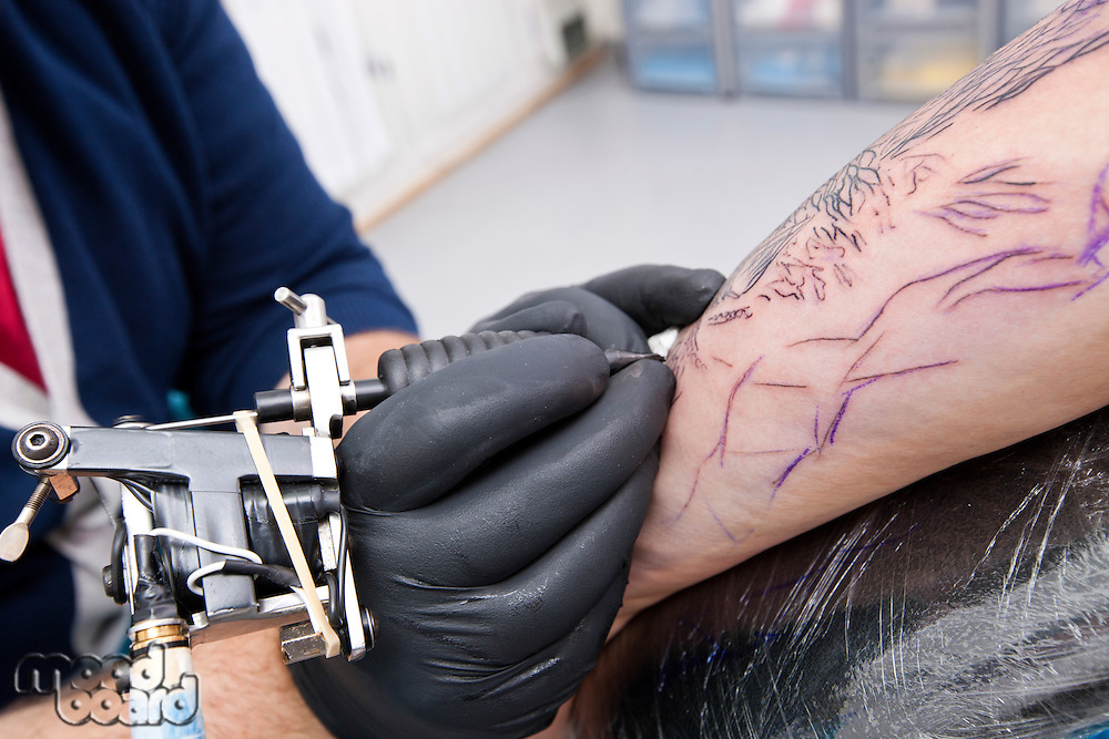 Cropped image of artist tattooing man's arm in tattoo parlor