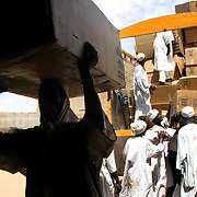 June 7, 2004 - Sudanese men working for CARE offload plastic sheeting at a CARE warehouse in Nyala, South Darfur where it will then be distributed to IDP's throughout the region. Photo by Evelyn Hockstein/CARE