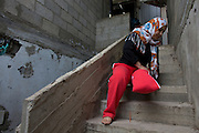 Palestinian woman Safa Fayez , 29 , as she pulls herself up the stair case of her home in Beit Hanoun ,Gaza  December 11,2014 . She was seriously wounded by shrapnel during last summer's war in Gaza between Israel and the Palestinian militants in the Hamas controlled Gaza Strip when  IDF shells hit the UN school crowded by hundreds of Palestinians seeking shelter . The attack on July 24,2014 killed at 15 Palestinians and wounded many including her baby and husband . She is a mother of four children and said that she had just left the classroom she was staying in with her family and heading outside to wait for a bus that the Red Cross was providing to evacuate the displaced to a safer area when the attack occurred . (Photo by Heidi Levine/Sipa Press).
