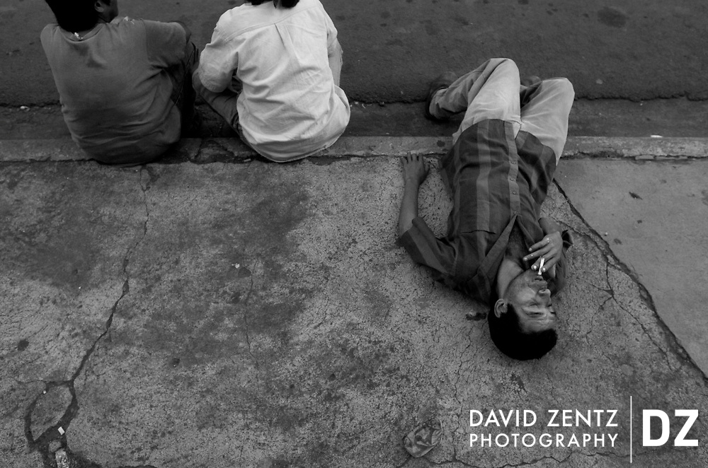 An inebriated man lays on the sidewalk during a political rally for socialist political leader Daniel Ortega at a Sandinista party rally in Jinotepe, Nicaragua on October 1, 2004.