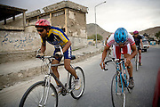 Afghan Cycling Federation national team members Abdull Qader Fahim, center, and Hashmat Ullah Barekzay, right, train on the streets of Kabul, Afghanistan. The ACF's national cycling team  now has roughly 15 men, 15 juniors, and 10 women who have participated in local, regional, and international races including the Southeast Asian Games.