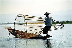 BURMA (MYANMAR) Shan State, Nyaungshwe, Inle Lake, 2006. Trapping his catch between a conical net and the shallow lake bottom, this Intha fisherman?s hard work is not rewarded often enough.