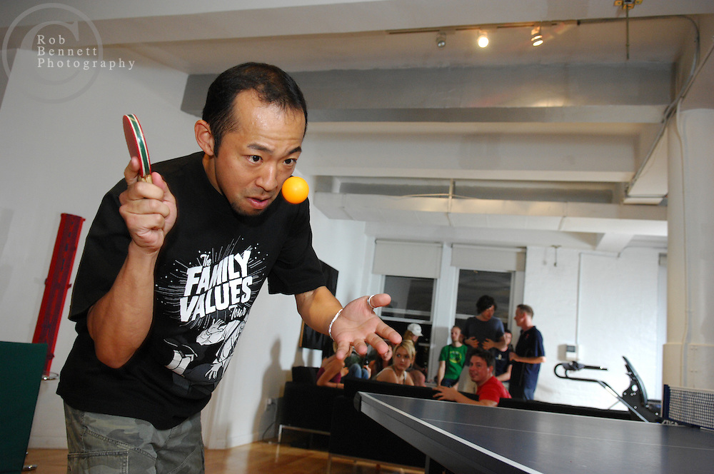 "Here, Kazuyuki Yokoyama, a former professional player in Japan, focuses on a match while a group socializes in the background. Yokoyama is using a miniature paddle to level the playing field against a lesser opponent..---.New York, NY- Friday, August 10, 2007 - ""Naked"" Ping Pong Tournament/Party-  An eclectic collection of city residents gather for a recurring Friday-night table tennis tournament/party at the Naked Ping Pong Club in the TriBeCa area of Manhattan. The founders of Naked Ping Pong are a trio of filmmakers (most recently, Naked Yoga) - Bill Mack, 34, Franck Raharinosy, 32 and Jonathan Bricklin, 30 - who claim to be training for the 2012 Olympics in London.. .Credit: Rob Bennett for The New York Times"
