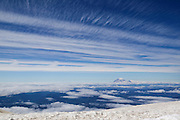 The jet stream streaks high above Mount Rainier, the tallest mountain in Washington state, in this view from the summit of Mount Adams. Jet streams are fast-flowing, narrow air currents. Shown here is the northern hemisphere polar jet, which flows over the middle to northern latitudes of North America, Europe, and Asia and their intervening oceans, typically between 23,000-39,000 feet (7-12 km) above sea level. Mount Rainier is 14,410 feet (4,392 meters) tall. Both Rainier and Adams are volcanoes.