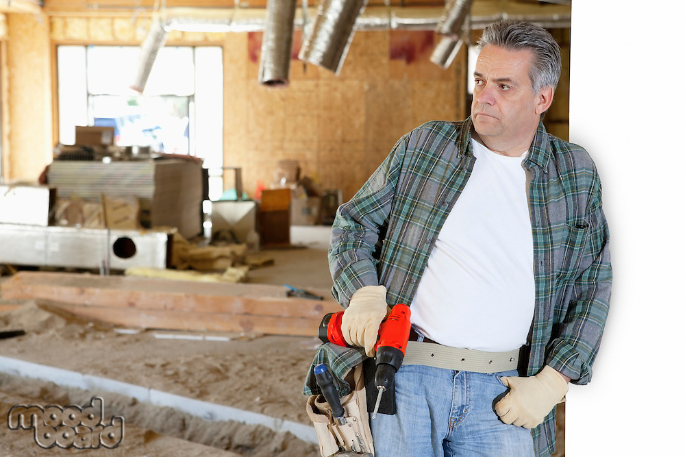 Front view of construction worker holding drill while leaning on white wall