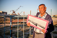 A former fisherman of the villege shows a picture of the old port in Aralsk, Kazakhstan. The picture he holds is exact same place of the background and now the seabed is completely exposed.