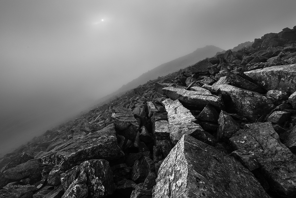 On the summit in dark swirling cloud. A delicate sun glimmered through the vapour, illuminating shards of quartz-covered, shattered wet rock. <br /> <br /> I was alone on the summit and it helped create the feeling that this pictorial wonder was my privilege alone.