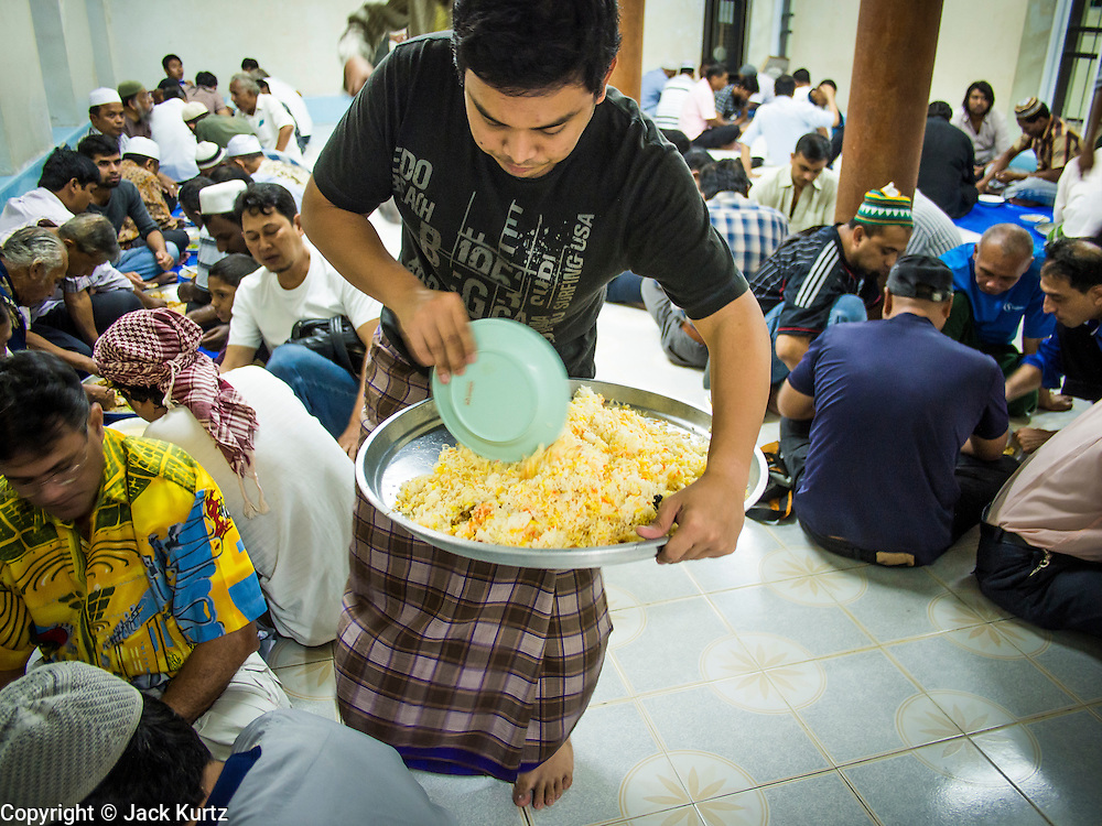 13 JULY 2013 - BANGKOK, THAILAND:  A man serves Iftar (the Muslim meal that breaks the day long fast) at Haroon Mosque in Bangkok during Ramadan. Ramadan is the ninth month of the Islamic calendar, and the month in which Muslims believe the Quran was revealed. The month is spent by Muslims fasting during the daylight hours from dawn to sunset. Fasting during the month of Ramadan is one of the Five Pillars of Islam. Muslims believe that the Quran was sent down during this month, thus being prepared for gradual revelation by Jibraeel (Gabriel) to the prophet Muhammad.        PHOTO BY JACK KURTZ