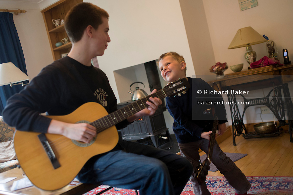 A 16 year-old teenager and his 4 year-old cousin play guitar together in the family living room.