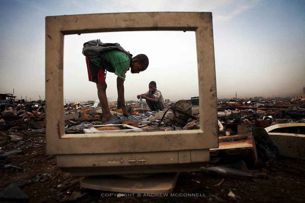 Children break apart CRT monitors to salvage metal from inside, at Agbogbloshie dump. Many children work at the dump salvaging metals which they sell to middlemen. They do not wear any protective clothing and so expose themselves to lethal doses of hazardous chemicals like mercury and lead.