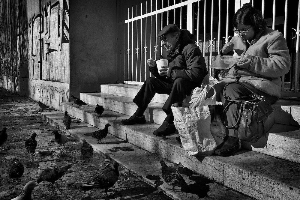 """Homelessness since March, Former Portuguese Army officer Captain Alberto Rodrigues, 70, who was in the Army for 11 years (66-68 Guinea Bissau, 68-70 Macau and 70-77 Mozambique), has some soup as his wife Natalia Gusmao, 50, eats some food by the stairs of a closed Christmas gift shop, after they have receiving a lunch at a free food distribution centre nearby """"Praça de Espanha"""" square (or Spain square), in Lisbon, Portugal, on November 28, 2012. Around 1.4 million people are currently unemployed in Portugal, and only 370,000 of them have receiving monthly social support from the government, leaving around 1 million people without the benefit. Over youths, unemployment rates is breaking records reaching 39% in the third quarter of the year, or equivalent to more than 175,000 people. The official unemployment rate in Portugal is currently on 15.7%, a bit away from the highest European rate in Spain, with 25.8%, followed by Greece with 25.1% of jobless. Photo by Mauricio Lima for The New York Times"""