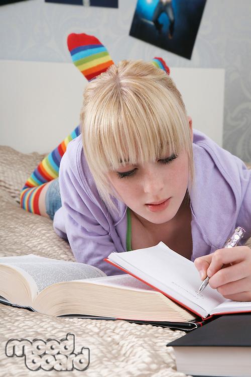 Teenage girl (16-17) doing homework on bed