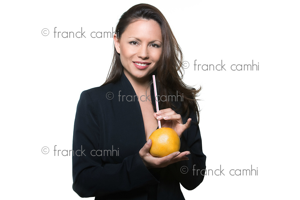 Portrait of beautiful mature woman holding orange and straw in studio isolated on white background