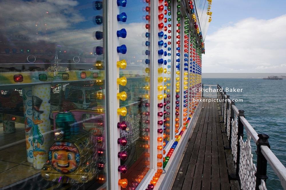 Brighton pier amusement arcade lights with the sea horizon beyond.