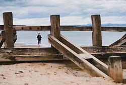 Portobello, Edinburgh, Scotland, UK. 4 April, 2020. On the second weekend of the coronavirus lockdown in the UK, a lone female runner on Portobello Beach takes her daily allowable outdoor exercise.