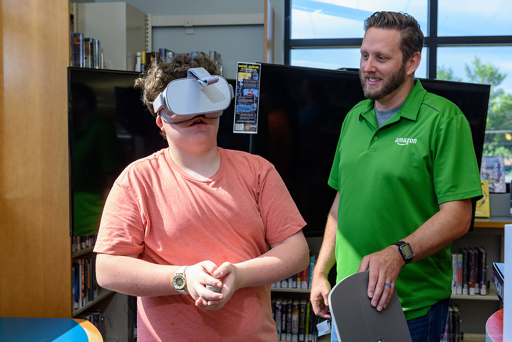 Isaac Stepp, 14, describes his experience wearing virtual reality goggles to Amazon Site Leader Brett Gorin. Leaders from Amazon present a donation of $10,000 in new technology to support Bullitt County Library's STEM and STEAM programs for students in the Bullitt County School District Tuesday, July 10, 2018 at the Ridgway Memorial Library in Shepherdsville, Ky. The donation will enhance the library's current Digital Tech and Makerspace Lab programs and ignite more students to take advantage of STEM education outside of the classrooms and included Oculus Go headsets, a Cubelets classroom, and several sets of LEGOs that will increase the lab's ability to help students learn and explore STEM. (Photo by Brian Bohannon)