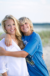 blond brother and sister smiling and embracing outdoors at the beach in East Hampton